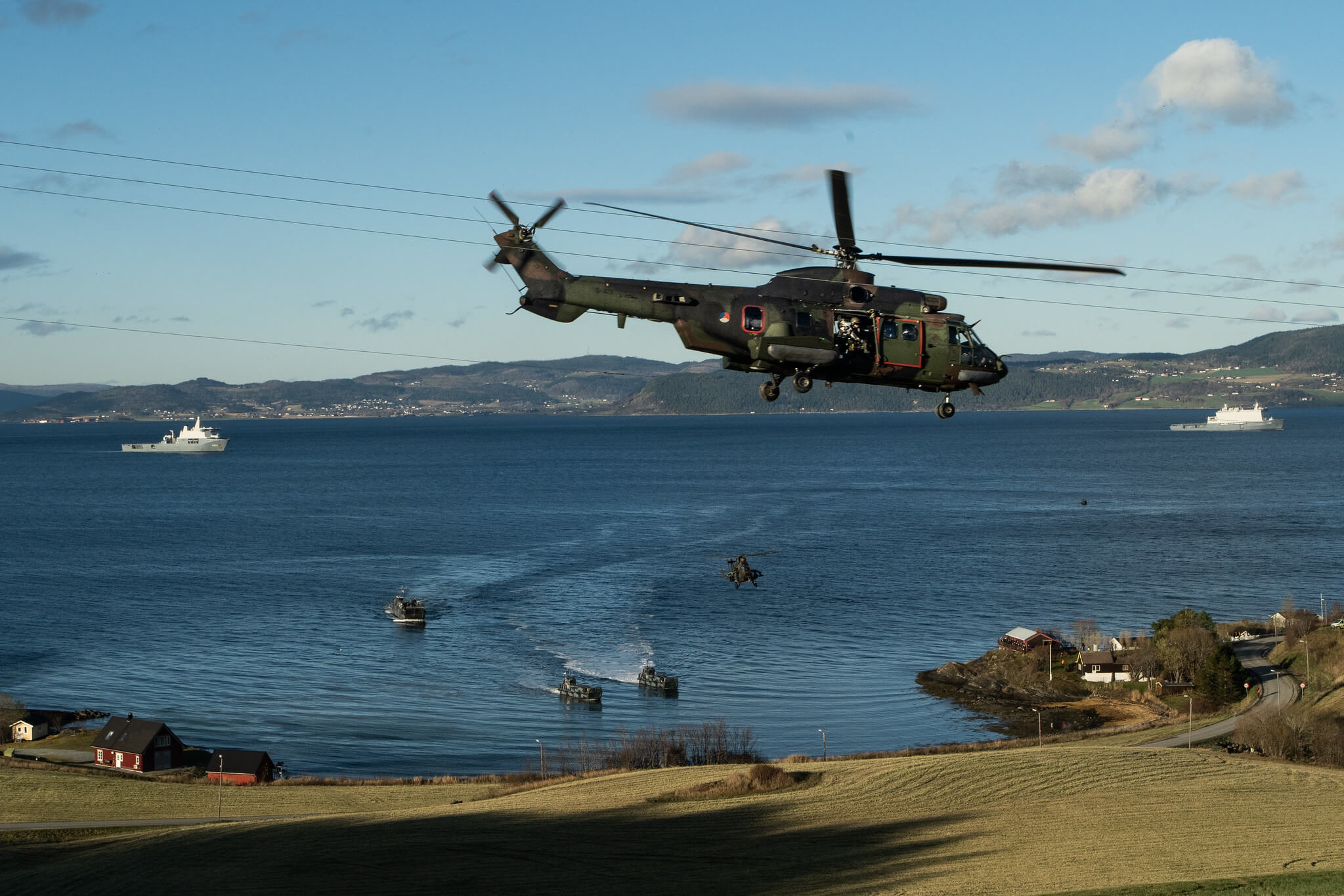 Boxhoorn - A Dutch Cougar helicopter takes off while NATO forces prepare to make an amphibious landing at a media event held during Exercise Trident Juncture 18 in 2018. NATO