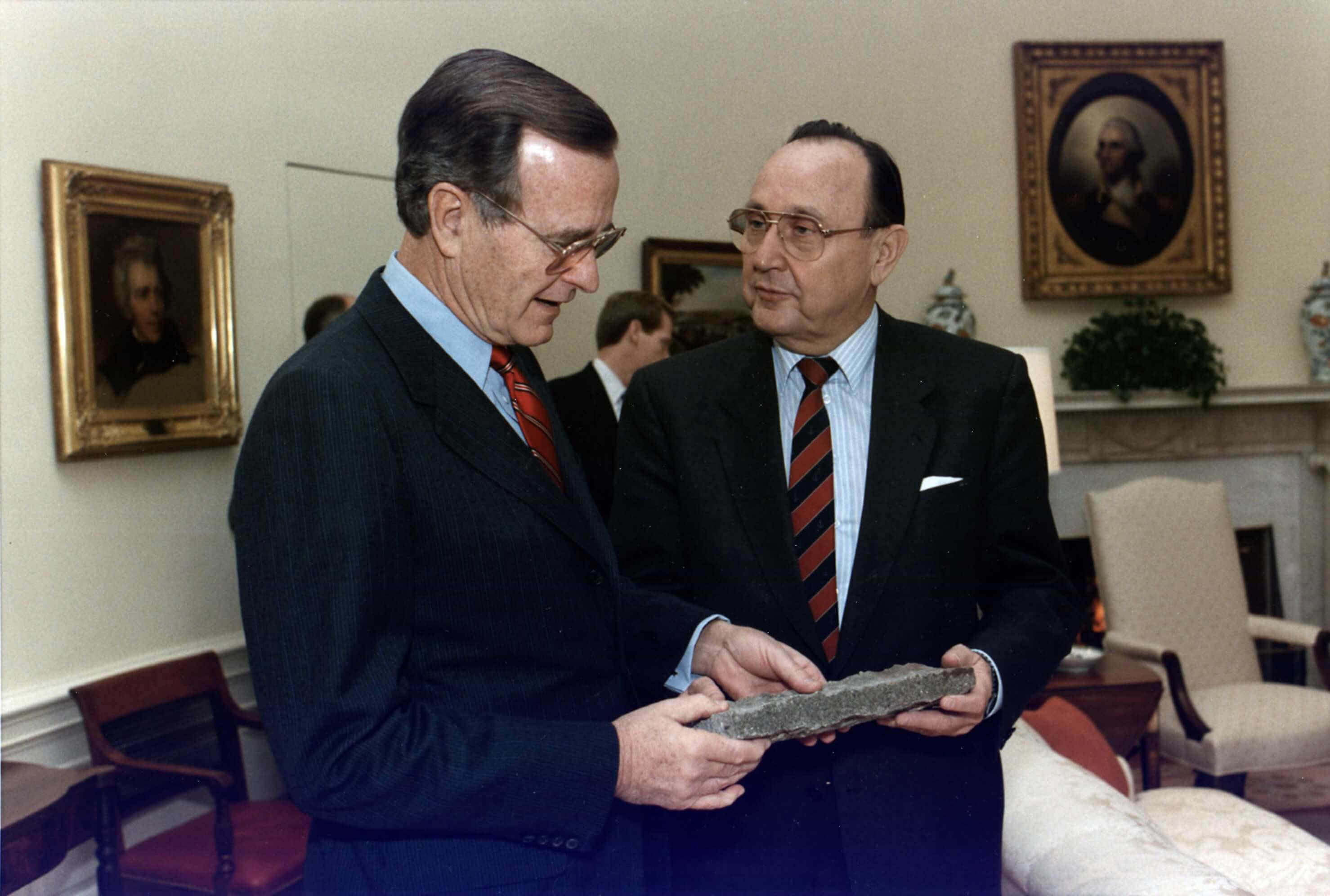 De toenmallige Amerikaanse president Bush (sr) ontvangt een stuk Berlijnse Muur van de West-Duitse minister Genscher in Washington op 21 november 1989. © Wikimedia Commons