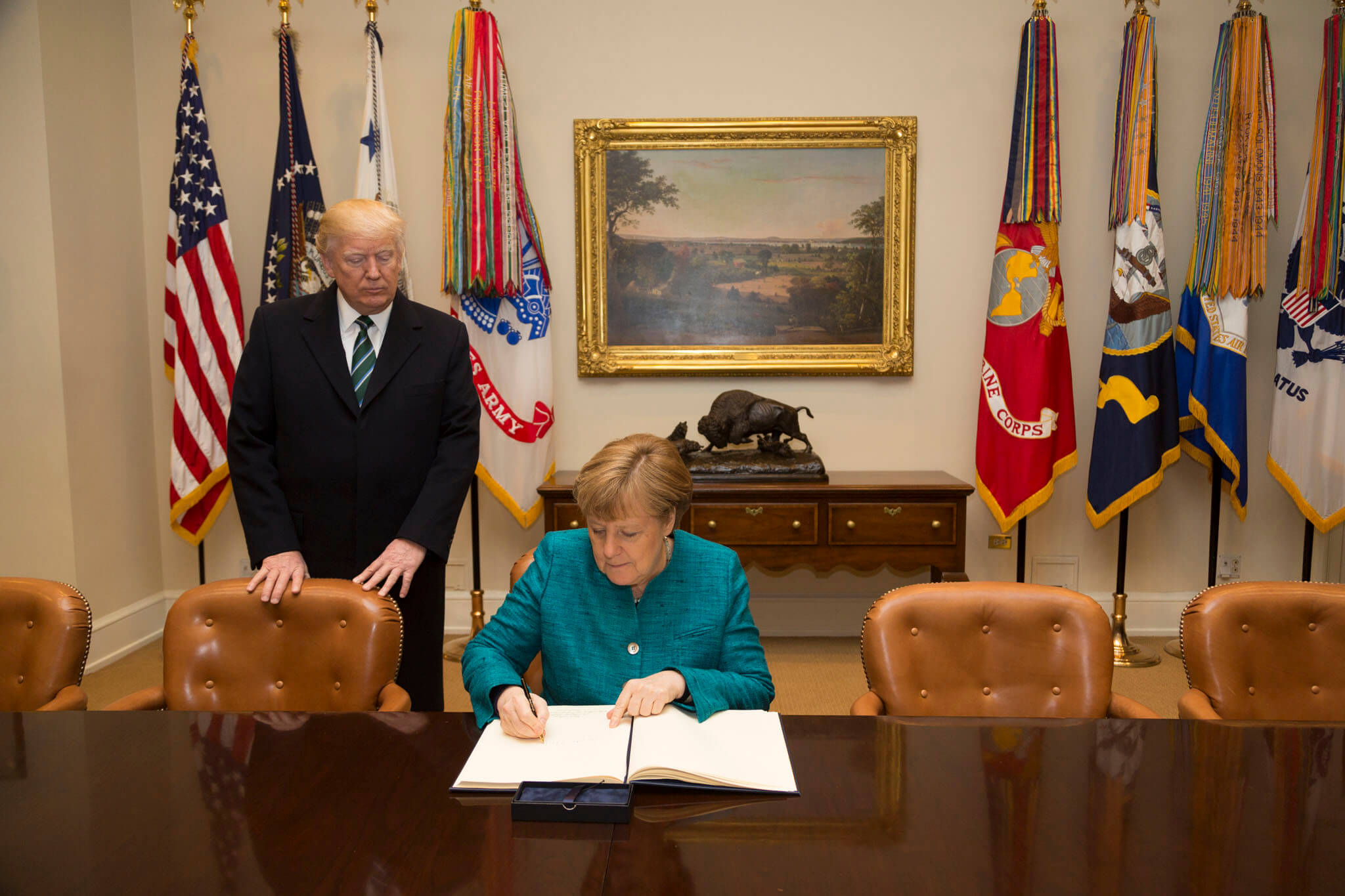 Frohlich-President Donald Trump accompanies German Chancellor Angela Merkel as she signs the guest book, Friday, March 17, 2017, in the Roosevelt Room, during her official visit to the White House in Washington in May 2018. Official White House Photo
