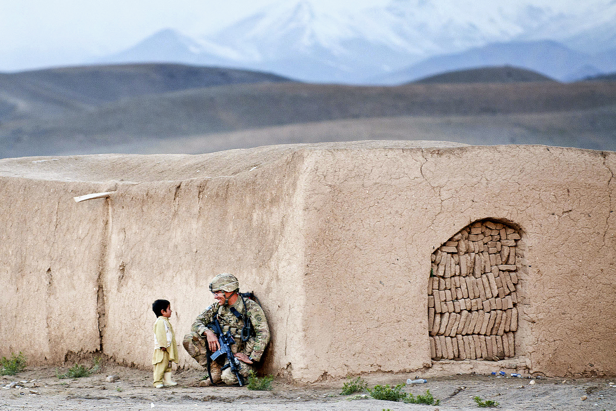 US soldier chatting with Afghan child