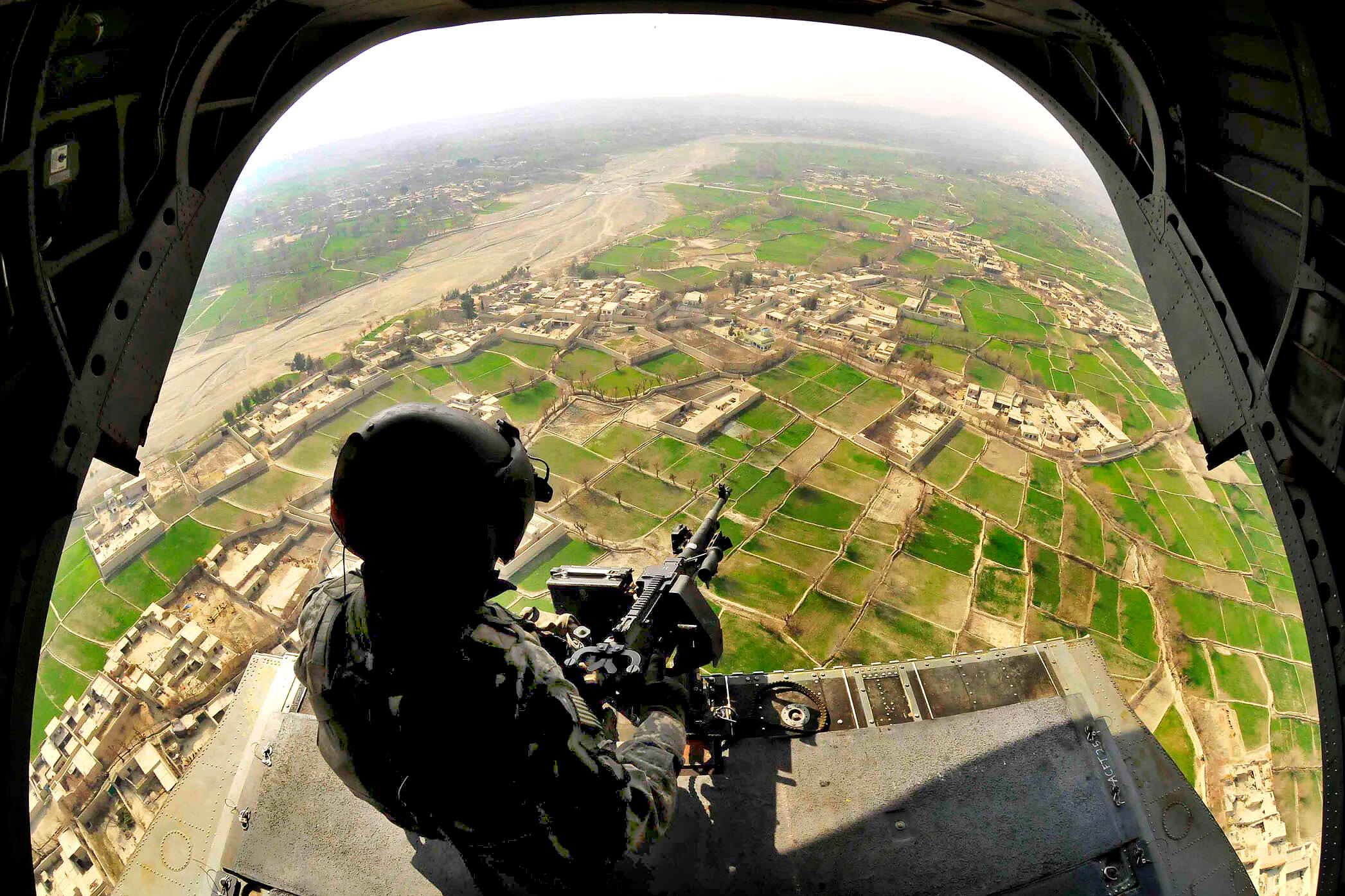 Kamminga-foto2-Sgt. 1st Class James Lee provides aerial security from the rear door of a CH-47 Chinook helicopter over the Khost province in eastern Afghanistan24b feb 2010-The U.S. Army-Flickr