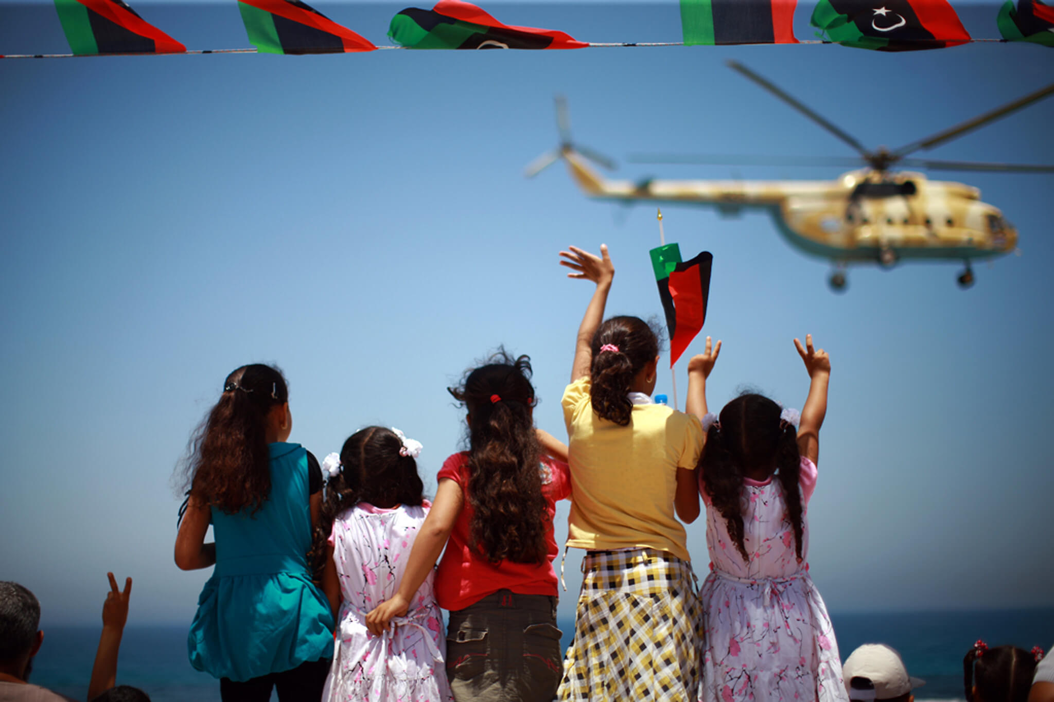 Girls wave and flash victory signs at a passing helicopter during a military parade in the western city of Zawiya, Libya, held to mark the anniversary of an uprising last year that cleared the way for the anti-Qadhafi forces' march on Tripoli.