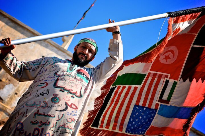 VanHeek- A Libyan man in 2011 showing a unity flag of countries that assisted the Libyan revolution. Aslan Media - Flickr
