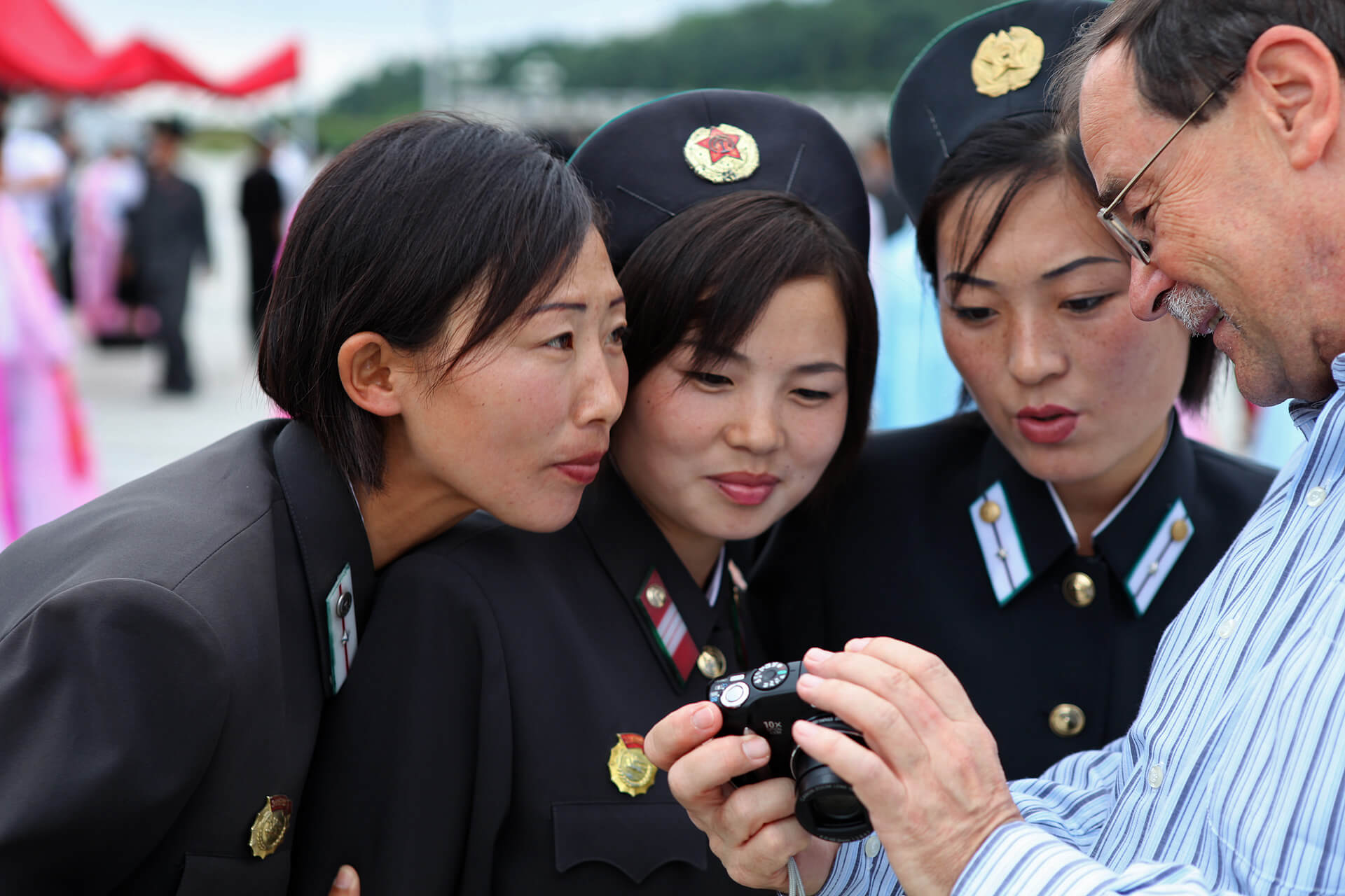 A tourist shows his pictures to North Koreans in the capital