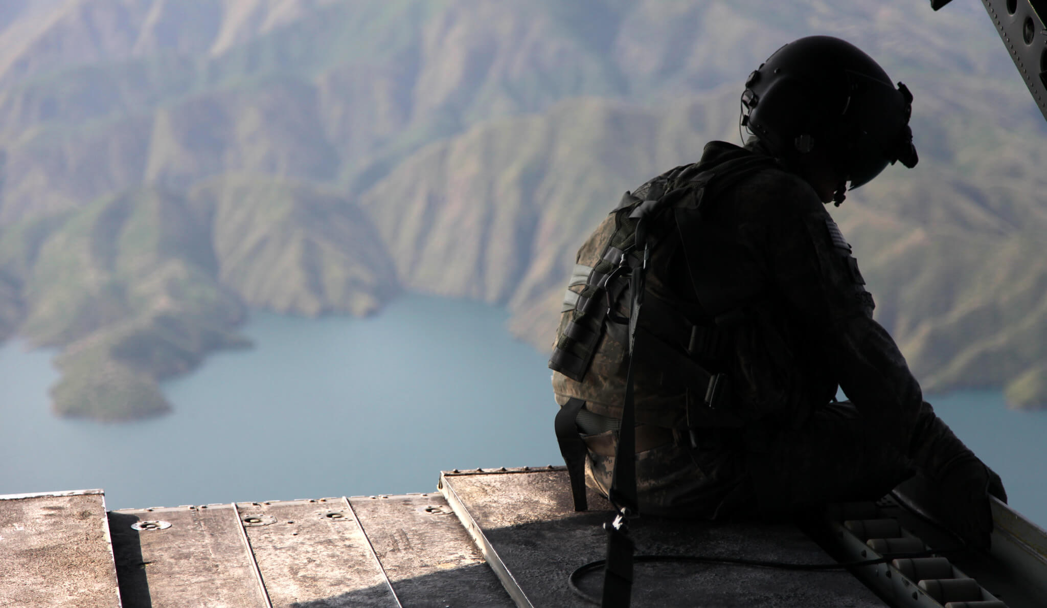 U.S. Army soldier observes the scenery while he sits on the ramp of a CH-47 Chinook in Khyber - Pakhtunkhwa, Pakistan. In 2010. a flood affected nearly 20 million Pakistanis, forcing many from their homes. © U.S. Army photo