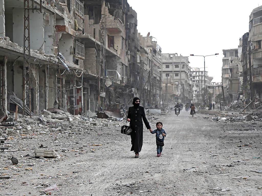 A Syrian woman and child walk down a destroyed street in Arbin, Ghouta region. ©Flickr/Jordi Bernabeu